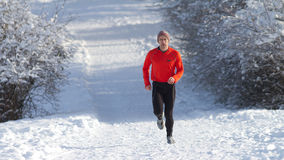Running athlete in the snow. Athlete running in the snow Royalty Free Stock Images