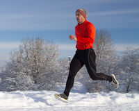 Running athlete in the snow Royalty Free Stock Image