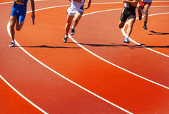 Running athletes. At stadium in relay race athletics competition stock photo