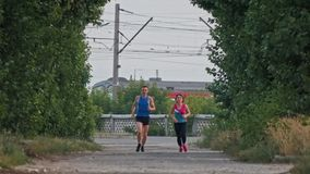 Running athletic couple runners training in park, over the train stock video
