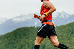 Running athletic male. With watch on hand on background mountains and green forest Stock Photos