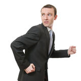 Running away. Stressed businessman running away looking back Stock Photo