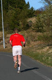 Running away. A man running on a forest path, training for a marathon run Royalty Free Stock Photography