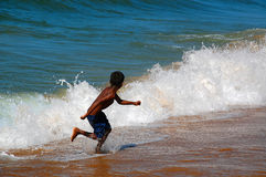 Running Away from the Waves Royalty Free Stock Images