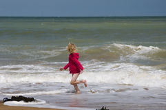 Running away from the waves Royalty Free Stock Image
