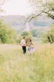 Running back de sourire heureux de couples dans le jardin de fleur tenant des mains Photos libres de droits
