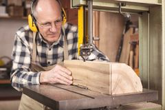 A running bandsaw with a carpenter working it stock photography