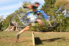Running The Barriers. Rider running the barriers during a cyclocross bicycle race Stock Photography