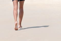 Running on beach. Running bare legs of runner jogging on beach. Shallow depth of field, focus on left foot Royalty Free Stock Photos