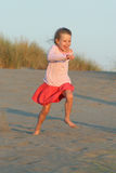 Running on the beach. Little girl running on the beach at sunset stock photo