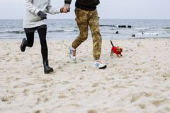 Running on the beach with dog stock photo
