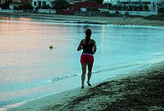 Running on the beach. A girl is running on the beach at sunset time royalty free stock images