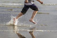 Running on beach making splashes. Stock Images