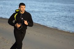 Running on the beach. The man in sportswear with earphones is running outdoors on the beach Royalty Free Stock Image