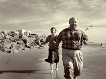 Running On the Beach Together. Part of my sepia toned retired couple on the beach series. Keyword series1rc to see the entire series with background and detail Royalty Free Stock Image