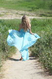 Running beauty. Blond running girl in the blue dress on the green background Royalty Free Stock Photography
