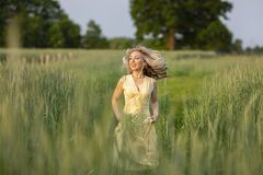 Running blonde girl on the field. Life in the country stock photos