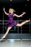 Running blonde girl in purple dress Stock Photos