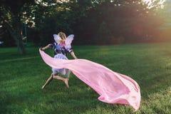 Running blonde white Caucasian child kid girl with long hair wearing pink fairy wings and tutu tulle skirt. Portrait of running blonde white Caucasian child kid Stock Photos