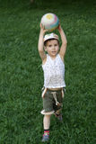Running boy with a ball. The cheerful running boy with a ball on a green grass in the summer Stock Image