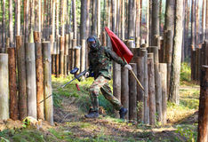 Running boy with paintball gun and red flag Stock Photos