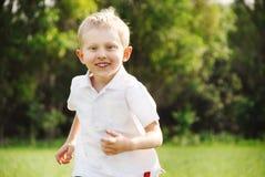 Running boy portrait. Portrait smiling little boy running in outdoor Royalty Free Stock Image