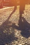Running Boy Shadow on Cobblestone Pavement Stock Photos