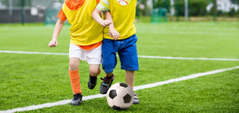 Running boys playing football soccer match. Kids playing football soccer match Stock Image