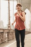 Running on Brooklyn bridge. Woman practicing jogging on the Brooklyn bridge stock photos