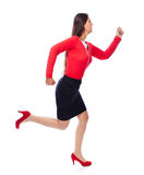 Running business Woman. Woman in red running sideways, is short on time isolated on White Stock Photography
