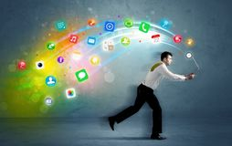 Running businessman with application icons from device Royalty Free Stock Images