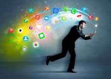 Running businessman with application icons from device Stock Photography
