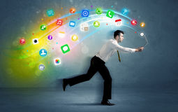 Running businessman with application icons from device Royalty Free Stock Photos