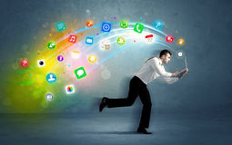 Running businessman with application icons from device Stock Images