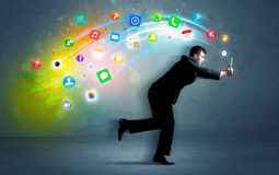 Running businessman with application icons from device Stock Photo