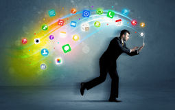 Running businessman with application icons from device Royalty Free Stock Photography