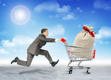 Running businessman with bag in shopping cart Royalty Free Stock Photo