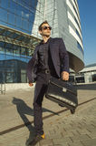 Running businessman with briefcase in hand. Walking around the office building Stock Photo