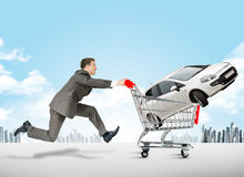 Running businessman with car in shopping cart. Running businessman with white car in shopping cart Stock Photos
