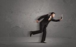 Running businessman with device in hand Royalty Free Stock Photo
