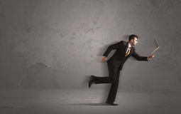 Running businessman with device in hand Royalty Free Stock Photos