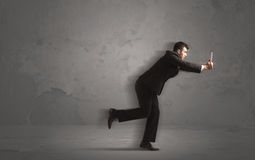 Running businessman with device in hand Stock Photos