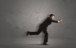 Running businessman with device in hand Royalty Free Stock Photography