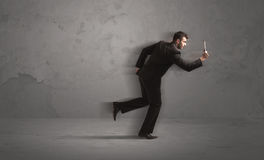 Running businessman with device in hand Stock Photography