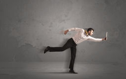 Running businessman with device in hand Royalty Free Stock Images