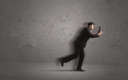Running businessman with device in hand Stock Photo