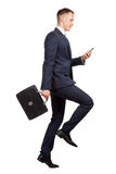Running businessman with his briefcase and mobile phone on white Royalty Free Stock Photo