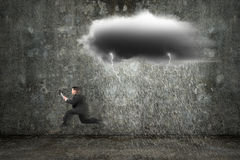 Running businessman holding tablet with dark clouds raining and Stock Photo