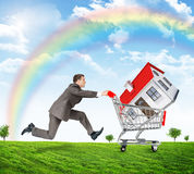 Running businessman with house in shopping cart Royalty Free Stock Photography