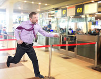 Running businessman in a hurry. On airport interior background Stock Photography